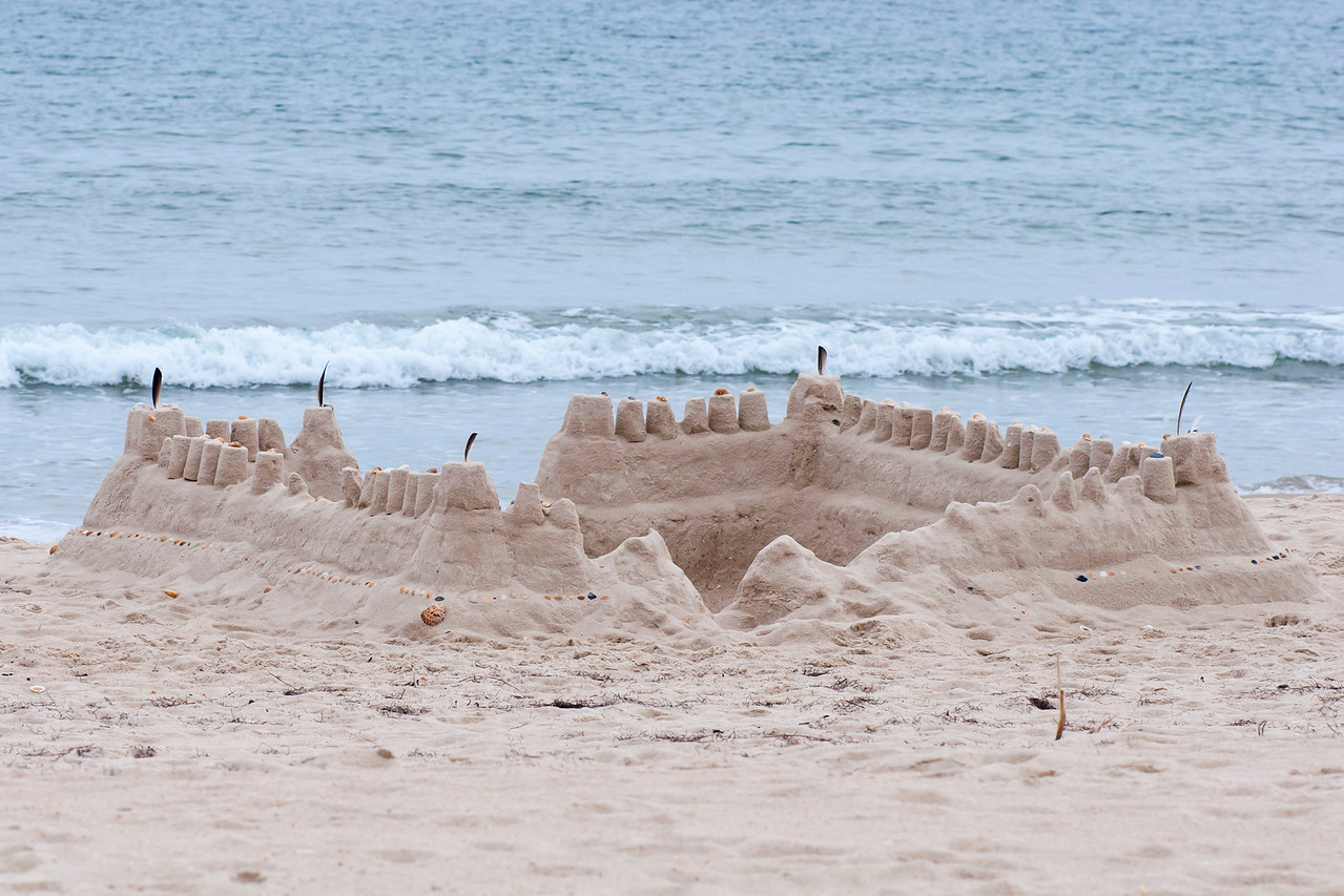 We rent a beach house on St. George Island when we go to Florida.  One day I noticed this fairly elaborate sand castle just down the shore.  Someone spent a lot of time creating this castle.  Notice the bird feathers that are planted at the corners.  Shells from the beach were used to decorate the top and sides of the castle.