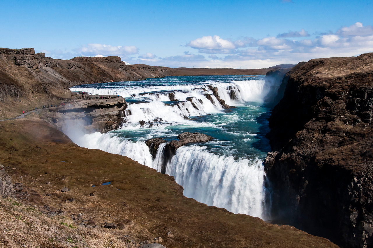 "One of the stops on the Golden Circle, a popular day tour for tourists out of Reykjavik, is the Gullfoss waterfall.  The Hvítá River flows over a three-step ""staircase"" to form this impressive waterfall."