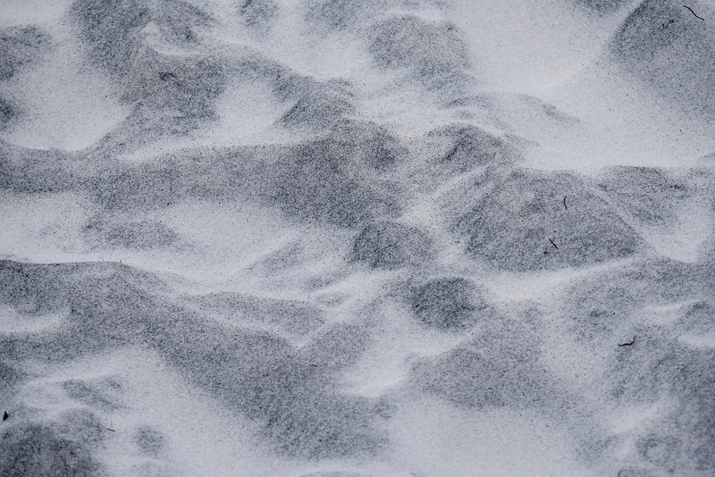 Here's another pattern in the sand.  This one looks like mountains seen from an airplane.  I think the darker areas are a more stable surface and the lighter areas are the sand that gets blown around the beach.