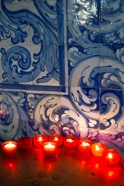 Candles in front of tiled wall in a church