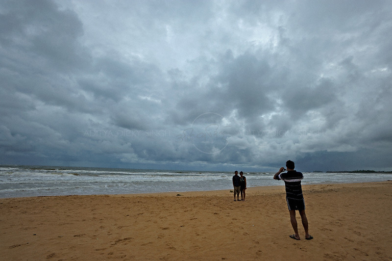 Tourists taking snap shots of each other in Bentota beach in Sri Lanka