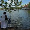 Pligrims feeding fish in the Kandy lake near the Sri Dalada Maligawa or temple of the tooth relic in Kandy, Sri Lanka