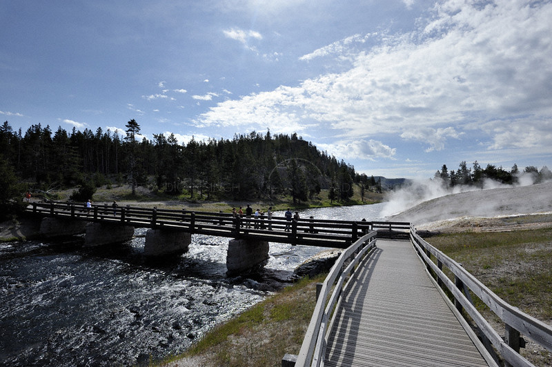Visitors over a wooden bridge during the summers in Yellowstone national park
