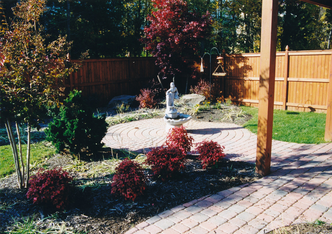 appian circle pattern paver patio and walkway with cedar fencing around perimeter of property.