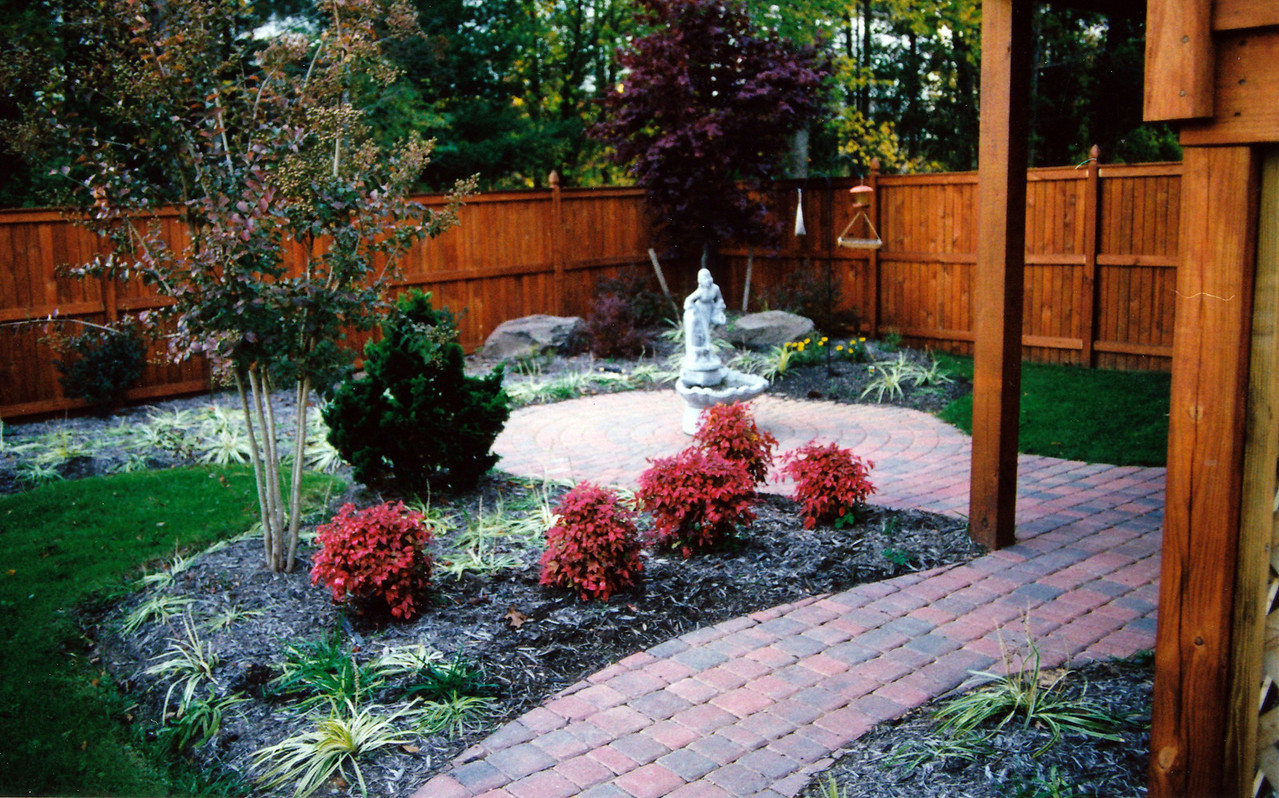Appian circle pattern patio and paver walkway with cedar fencing