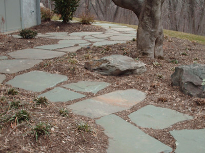 Irregular fieldstone patio & walkway with decorative boulders