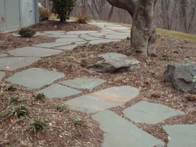 Irregular fieldstone patio & walkway with decorative boulders