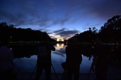 Photographers all trying to take a picture of the Lincoln Memorial and reflecting pool at sunset.
