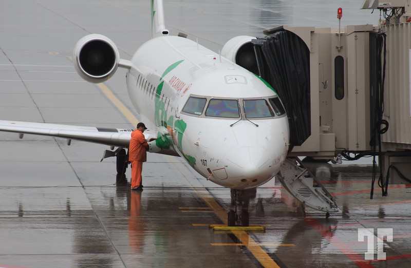 View of a Air Canada Jazz aircraft being refueled, at Thunder Bay airport on a rainy morning.