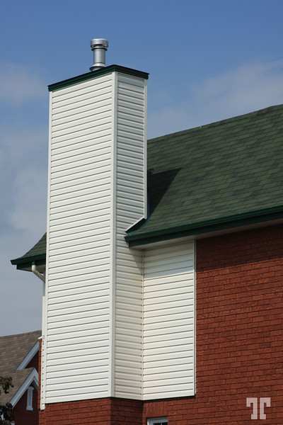 White cheminee of a new red house with a green roof. Gatineau, - Le Plateau- Quebeck, Canada