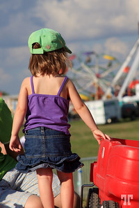 Little girl in the amusement park, looking at ferris wheel