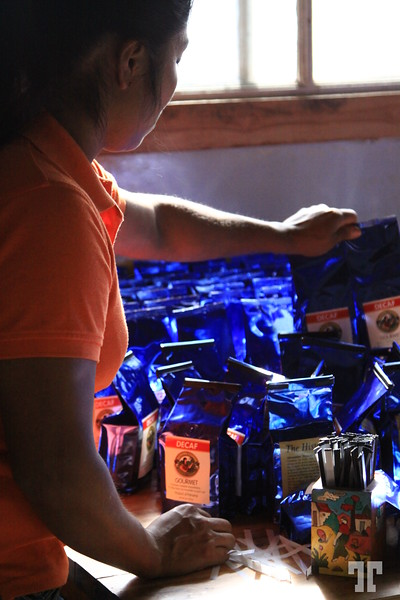 Packing the coffee<br /> <br /> We took a tour in a small coffee factory in Boquete, Panama, yesterday.<br /> <br /> This lady dressed in orange working with the blue (decaf) coffee packages attracted my eye (SOOC) :)