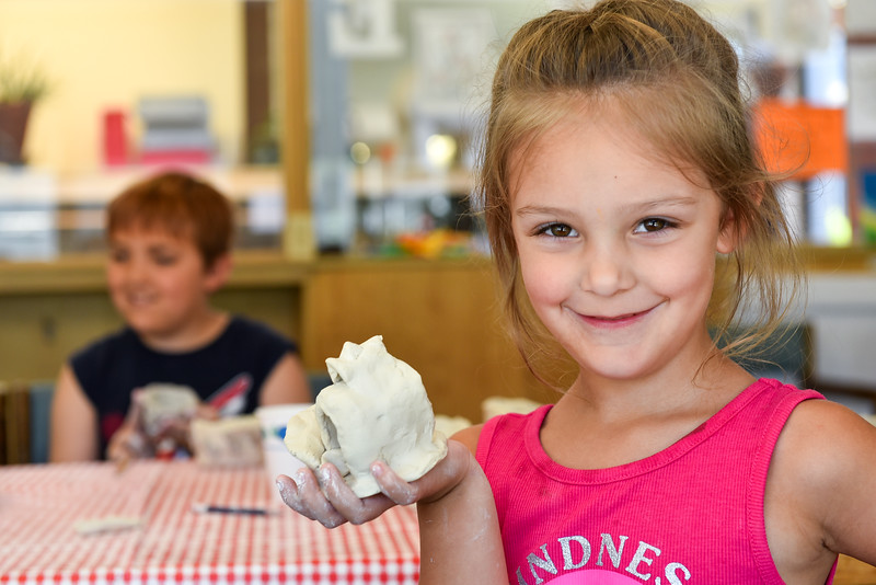 "Charlotte LaClair, 5, of Fitchburg shows off her own creation she calls ""Doube Bridge"" during a pinch pot making class at the Fitchburg Public Library on Monday.  SENTINEL & ENTERPRISE JEFF PORTER"