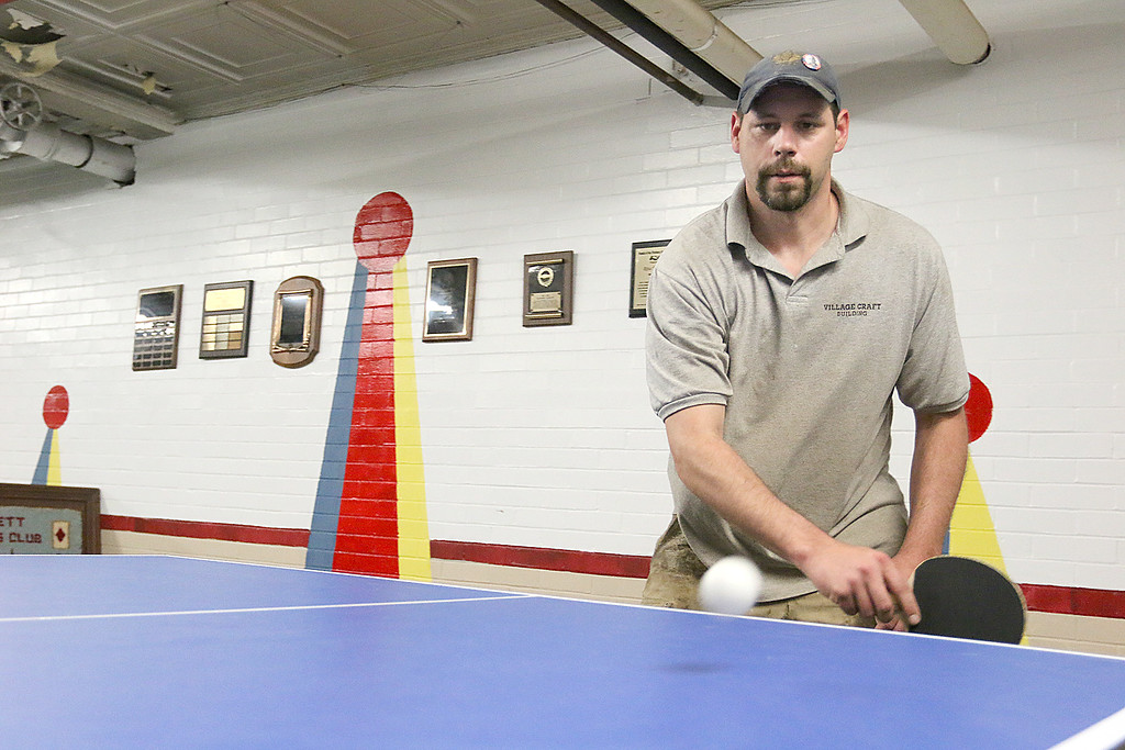. Nick Squailia, 36, visits the Senior Center on Thursdays to plays some ping pong with Darrel Hopkins, 72, and Ken Jones, 82. SENTINEL & ENTERPRISE/JOHN LOVE