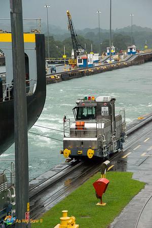 "Canal ""mule"" guiding ship through a lock in Panama"