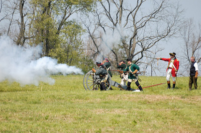 Stock image of British soldiers firing a cannon at the settler's fort during the re-enactment of the Ruddle's Station Massacre in Kentucky USA.  In 1780, during the Revolutionary War, British and Indian troops attacked the station in present-day Harrison County. Twenty settlers were killed; survivors were marched to Detroit and held for the rest of the war.