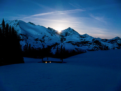 The full equinox/Easter moon breaks over the Old Hyndman and Cobb Peak ridgeline whil light glows from Pioneer Cabin.
