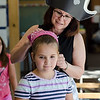 Alexis French, 8, gets a bandana tied on by June Celona during pirate day at the Fitchburg Public Library on Tuesday afternoon. SENTINEL & ENTERPRISE / Ashley Green