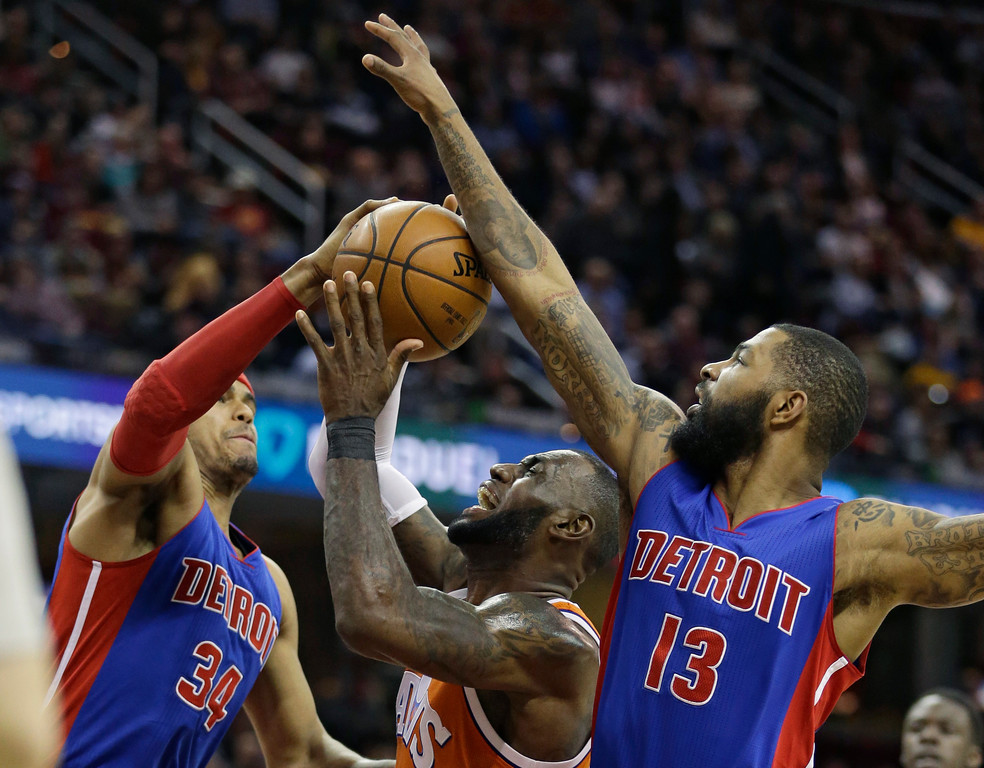. Cleveland Cavaliers\' LeBron James, center, drives against Detroit Pistons\' Tobias Harris, left, and Marcus Morris in the first half of an NBA basketball game, Tuesday, March 14, 2017, in Cleveland. (AP Photo/Tony Dejak)