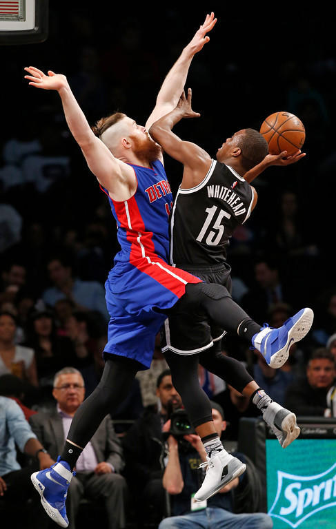 . Detroit Pistons center Aron Baynes (12) defends Brooklyn Nets guard Isaiah Whitehead (15) who tries to get a shot off during the first half of an NBA basketball game, Tuesday, March 21, 2017, in New York. (AP Photo/Kathy Willens)