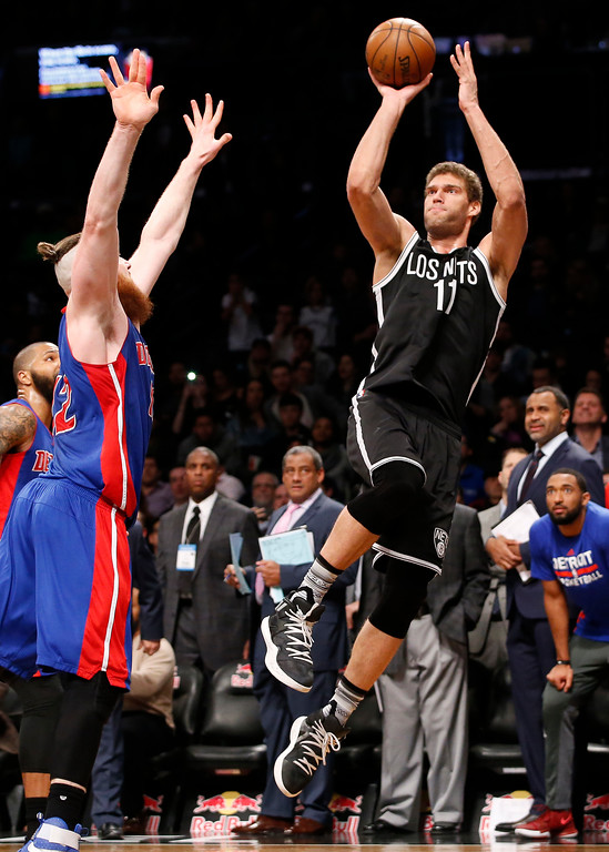 . Detroit Pistons center Aron Baynes (12) defends as Brooklyn Nets center Brook Lopez (11) goes up for two points to sink a buzzer-beater that lifted the Nets to victory over the Pistons during the second half of an NBA basketball game, Tuesday, March 21, 2017, in New York. The Nets defeated the Pistons 98-96. (AP Photo/Kathy Willens)