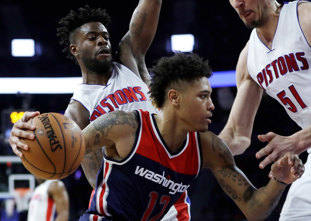 . Washington Wizards forward Kelly Oubre Jr. (12) drives on Detroit Pistons forward Reggie Bullock and center Boban Marjanovic, right, during second half of an NBA basketball game, Monday, April 10, 2017, in Auburn Hills, Mich. (AP Photo/Carlos Osorio)