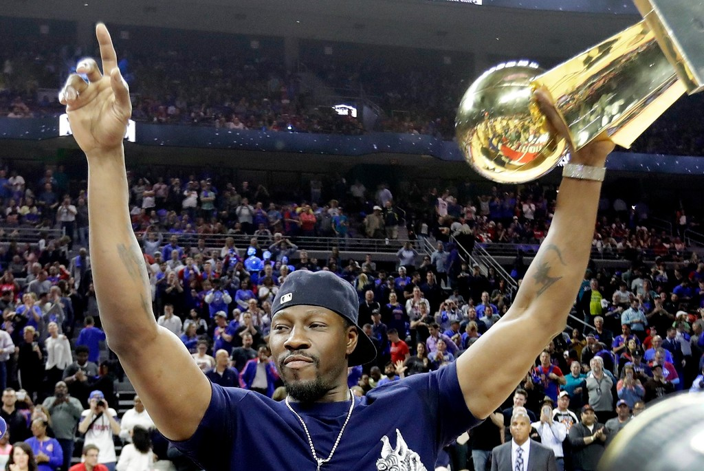 . Former Detroit Pistons center Ben Wallace raises the Larry O\'Brien NBA Championship Trophy won by the Pistons in 2004 during a halftime ceremony of an NBA basketball game, Monday, April 10, 2017, in Auburn Hills, Mich. The Pistons are playing their last game at the Palace before moving to downtown Detroit. (AP Photo/Carlos Osorio)