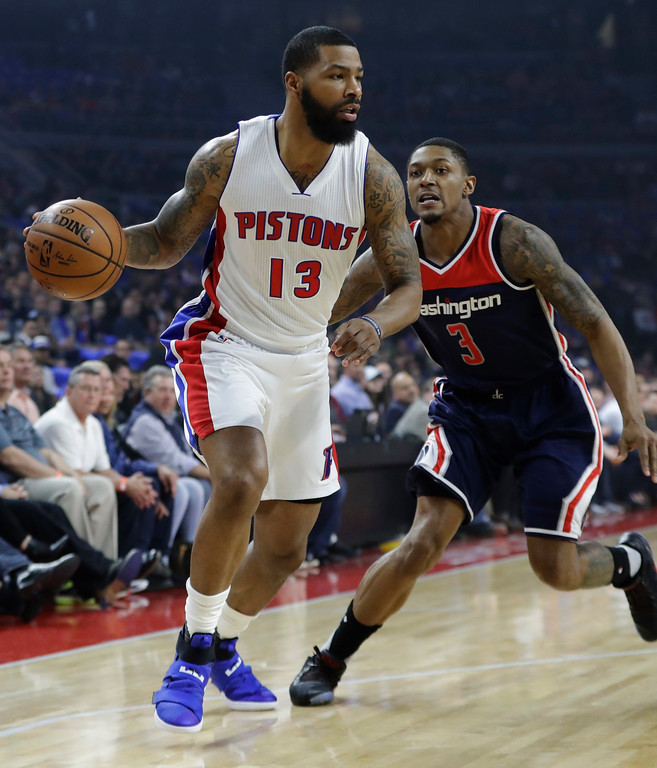 . Detroit Pistons forward Marcus Morris (13) drives around Washington Wizards guard Bradley Beal (3) during the first half of an NBA basketball game, Monday, April 10, 2017, in Auburn Hills, Mich. (AP Photo/Carlos Osorio)