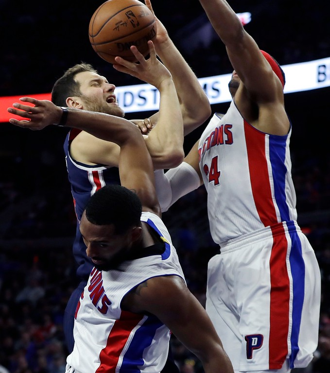 . Washington Wizards guard Bojan Bogdanovic shoots around the defense of Detroit Pistons guard Darrun Hilliard, left, and forward Tobias Harris (34)during second half of an NBA basketball game, Monday, April 10, 2017, in Auburn Hills, Mich. (AP Photo/Carlos Osorio)