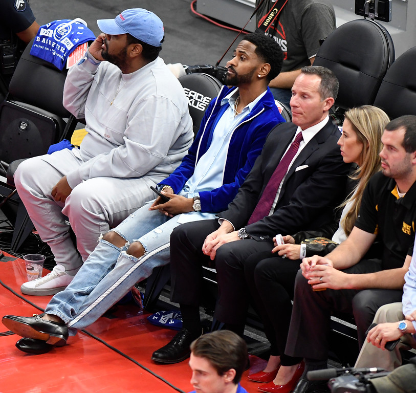 . From left, rapper Big Sean; Christopher Ilitch, president and CEO of Ilitch Holdings, Inc., and his wife Kelle Ilitch watch the Detroit Pistons play the Charlotte Hornets in the first quarter, Wednesday, Oct. 18, 2017 in Detroit.  (Special to The Oakland Press/Jose Juarez)