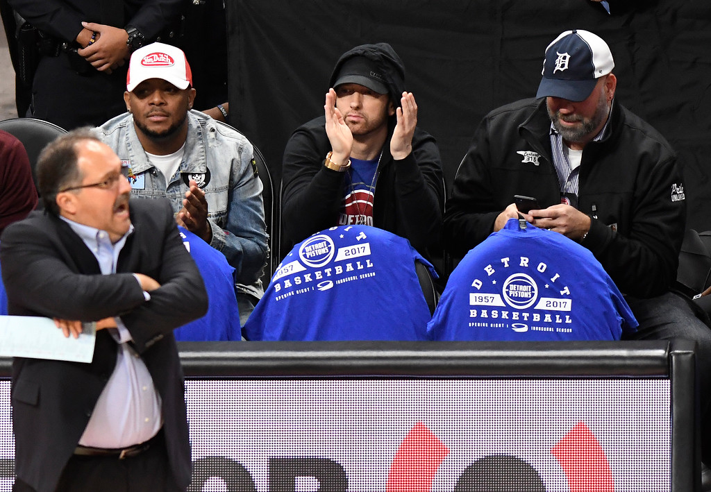. Rapper Eminem, center, cheers on the Detroit Pistons as they played the Charlotte Hornets in the first quarter, Wednesday, Oct. 18, 2017 in Detroit.  (Special to The Oakland Press/Jose Juarez)