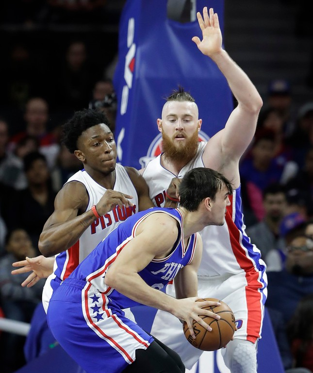 . Philadelphia 76ers forward Dario Saric looks to shoot around Detroit Pistons forward Stanley Johnson, left, and center Aron Baynes during the first half of an NBA basketball game, Monday, Feb. 6, 2017, in Auburn Hills, Mich. (AP Photo/Carlos Osorio)