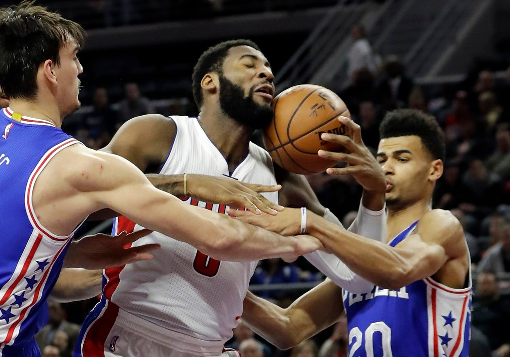 . Philadelphia 76ers forward Dario Saric, left, and guard Timothe Luwawu-Cabarrot (20) reach in on Detroit Pistons center Andre Drummond as pulls down a rebound during the first half of an NBA basketball game, Monday, Feb. 6, 2017, in Auburn Hills, Mich. (AP Photo/Carlos Osorio)
