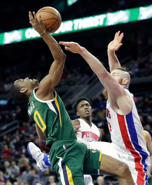 . Utah Jazz guard Alec Burks (10) loses control of the ball defended by Detroit Pistons center Aron Baynes during the first half of an NBA basketball game, Wednesday, March 15, 2017, in Auburn Hills, Mich. (AP Photo/Carlos Osorio)