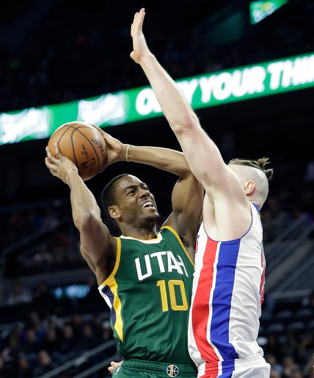 . Utah Jazz guard Alec Burks (10) is defended by Detroit Pistons center Aron Baynes during the first half of an NBA basketball game, Wednesday, March 15, 2017, in Auburn Hills, Mich. (AP Photo/Carlos Osorio)