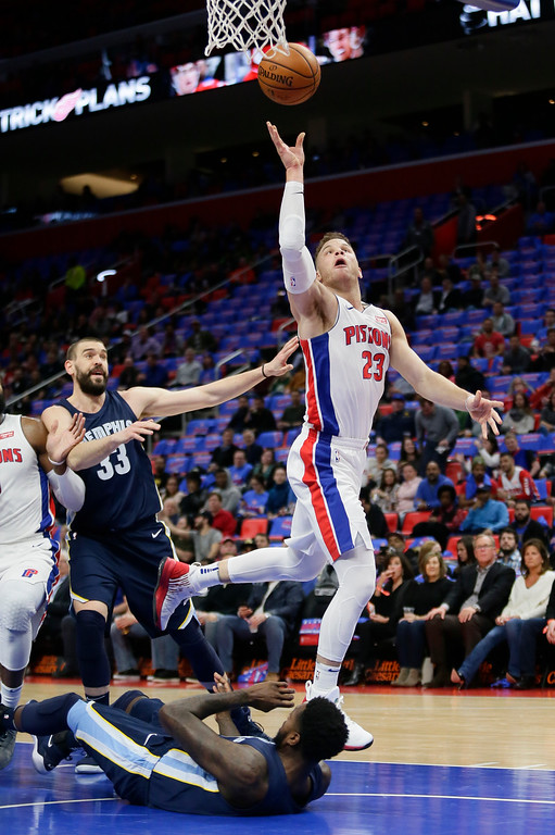 . Detroit Pistons forward Blake Griffin (23) gets a shot off after colliding with Memphis Grizzlies forward JaMychal Green, bottom, while going to the basket as Memphis center Marc Gasol (33) looks on during the first half of an NBA basketball game Thursday, Feb. 1, 2018, in Detroit. (AP Photo/Duane Burleson)