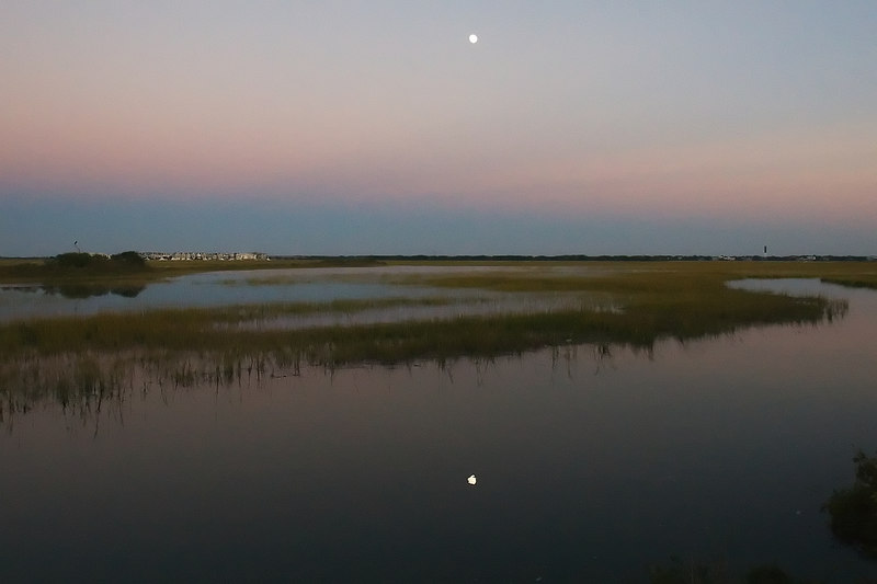 Back to the marsh side, it is darker.  The moon, three days from being full has gotten higher and is reflected in the creek.  The hillock can barely be seen, the condos appear small with that wider lens.  I included the Sullivan's Island lighthouse to my right.