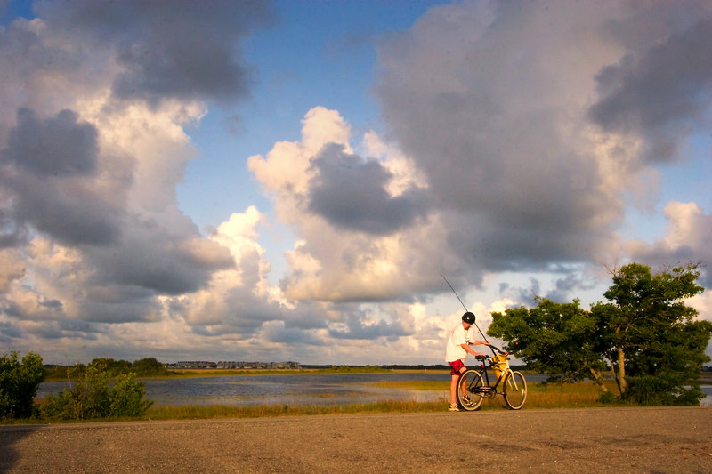 Carolina Evening: a low country marsh, and a boy on a bike with a fishing pole.  <br /> 6/24/2006