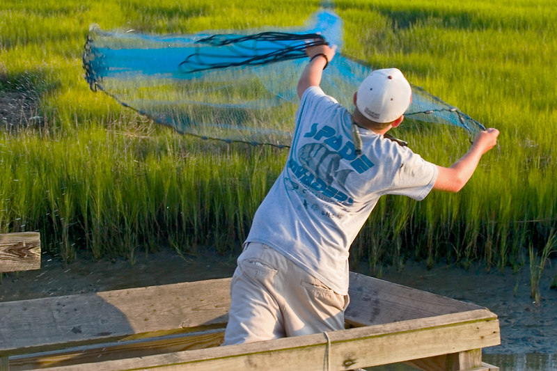 """Casting the fish net """"on the waters"""".  He is catching small minnow looking fish to use for bait for his pole and hook with which he catches """"dinner"""".<br /> <br /> I think it is all about the food for everyone!"""