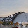A profile view of the Civic (mellon) Arena in Pittbsurgh, Pa.  This view from the side shows the steel structure on the roof dome with a line of autumn colorful trees.  Looking behind the Igloo, a portion of the new Console Energy Center can be seen.