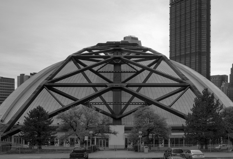 The structural steel of the Civic (Mellon) Arena along the roof dome.  This section is where the other panels slide into when the roof retracted.  The autumn season is changing the leaves on the trees that line the building which are enhanced by the twilight hour and colorful sky.