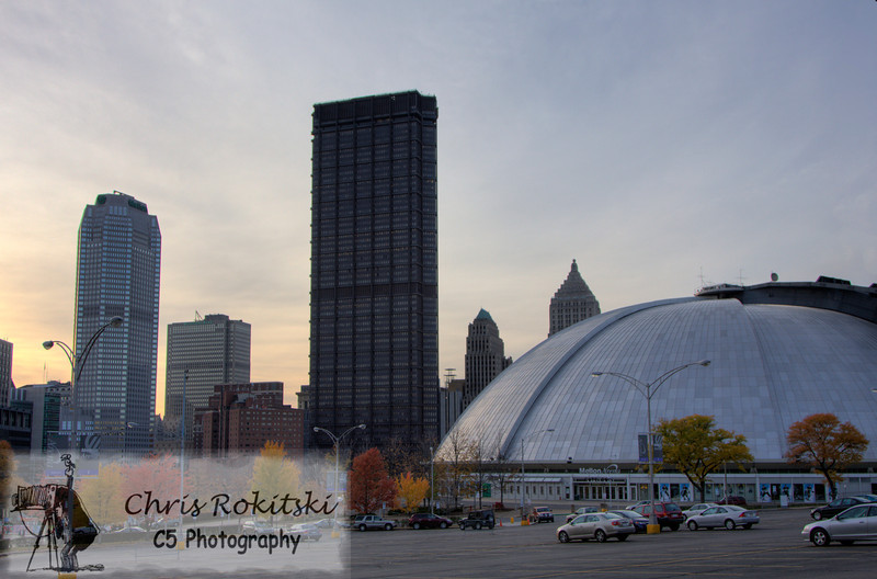 The Civic Arena (Igloo) standing in the foreground of the US Steel and the Mellon Buildings.  This was taken during a twilight hour to show beautiful, colorful sky in Pittsburgh, PA.  This was also in the autumn season as can be seen by the changing leaves of the trees in the parking lot.