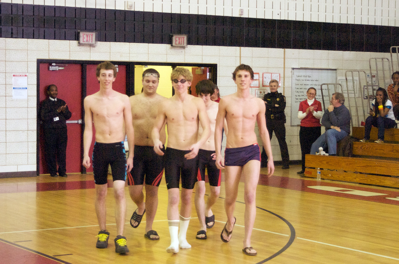 Lead by Kyle Mcmeken these five QO swimmers approach center court to join nine other senior swimmers during a half-time tribute to the QO swim team.