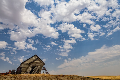 USA, Washington. Abandoned leaning schoolhouse in Palouse farm country amid blue sky with clouds
