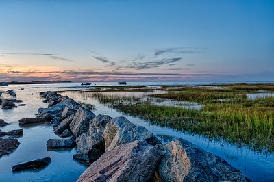 USA, Yarmouth Port, MA.  Boats anchored near the march grass at Mill Creek at sunset.