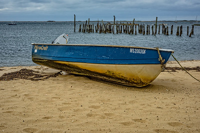 USA, Provincetown, MA. A dory tied up on the sand with remnants of wooden pier, birds and sailboats in the background