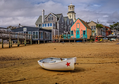 USA, Provincetown, MA. A dory tied up on the sand with colorful buildings of Provincetown in background.