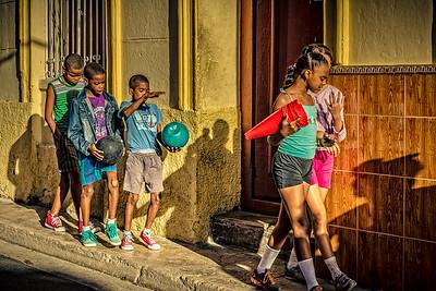 Cuba, Havana.  Group of children walking with balls and sports equipment.