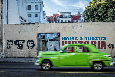 Vintage green car passes by revolutionary mural and slogan in Centro Habana