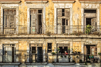 Cuba, Havana.  A woman in a red sweater can be seen in a window of a dilapidated building along the Malecon.